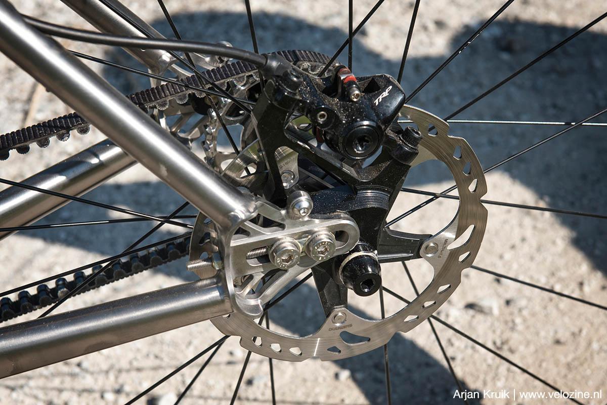 De remklauw wordt óók op de verschuifbare dropout gemonteerd. Verstel je het wiel, dan hoef je dus niet de remklauw opnieuw uit te lijnen.